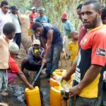 Villagers filling containers with first-time water